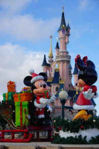 Mickey offering Minnie a Christmas gift, with castle in background